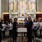 Anna Maria Veniero consegna al Coro Arcobaleno nella persona del M° Intoccia la targa di commemorazione per l'occasione. Sulla sinistra il M° Nicola Capano